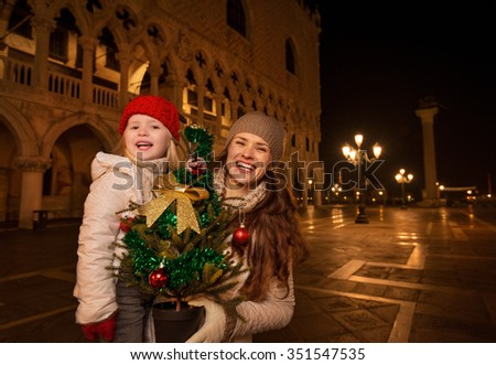 Holiday family trip to Venice, Italy can change the whole Christmas experience. Happy mother and child with Christmas tree on Piazza San Marco in the evening