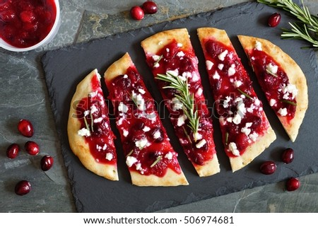 Holiday flatbread appetizer with cranberries and goat cheese, overhead scene on a slate background