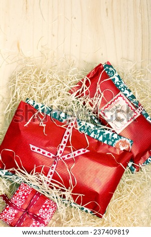Holiday gift boxes decorated with ribbon on wooden background - stock photo