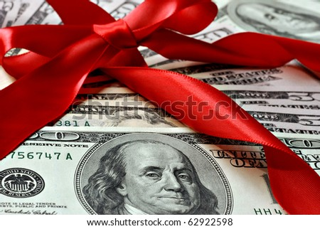 Holiday gift of money.  100 and 50 dollar bills with red satin ribbon.  Macro with shallow dof. - stock photo