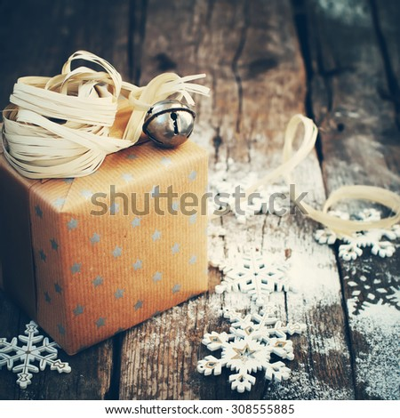 Holiday Gift with Jingle Hand Bell and Natural Twine on Wooden Background. Toned image - stock photo