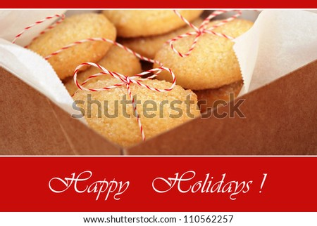 Holiday greeting card with macro image of sugar cookies tied with festive bakers twine in box.  Shallow dof with selective focus on string bow.