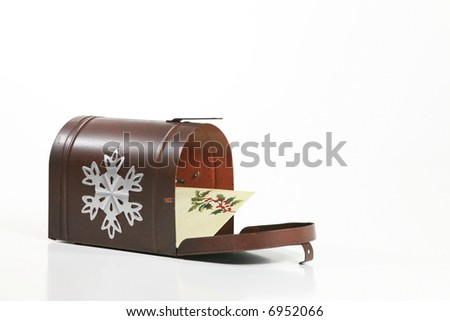 Holiday Greetings: A holiday envelope inside a wintry mailbox isolated against a white background. Space for copy. - stock photo