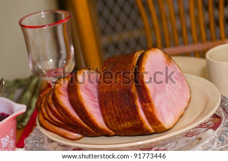 Holiday Ham on a Plate with a Wine Glass in the Background - stock photo