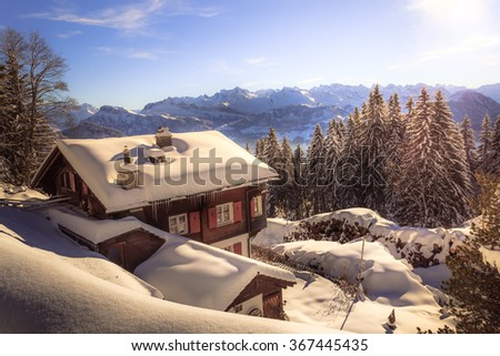 Holiday home in the winter with snow covering the landscape in the swiss mountains with view on a distant mountain range during sunset - stock photo