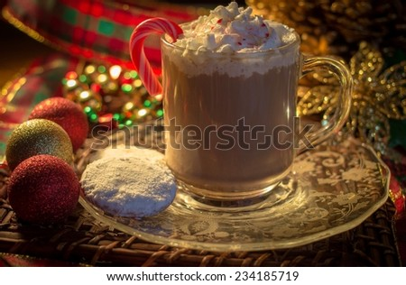 Holiday Hot Chocolate. Mug of hot chocolate with whipped cream and candy cane surrounded by elegant holiday decor.  - stock photo