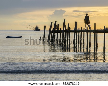 Holiday makers walk along a wooden pier at sunset on Ao Phrao Beach on Ko Kut island, east Thailand