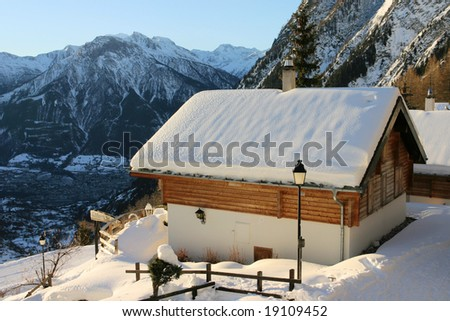 Holiday mountain house covered by snow in Tschuggen, Wallis, Switzerland