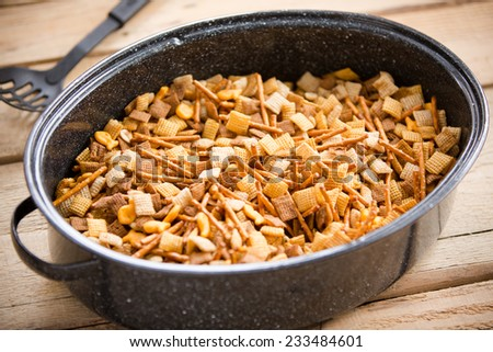 Holiday Party Food Mix - This is a shot of a party mix containing cereal, peanuts and pretzels in a roaster pan on an old wooden table. - stock photo
