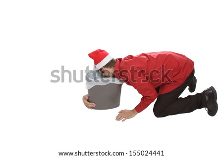 Holiday party gone wrong! This office worker vomits in a office trash can after consuming too much alcohol while embarrassing himself with his colleagues. - stock photo