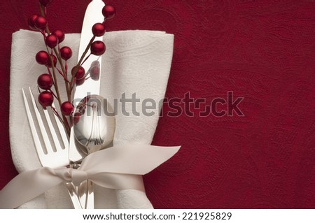 Holiday Place setting with Red Berries, Silverware, White Napkin and Ribbon on Rich Red Tablecloth Background with blank room or space for copy, text, words.  Horizontal above view, looking down. - stock photo