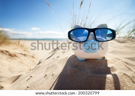 Holiday savings piggy bank on a beach vacation with sunglasses - stock photo