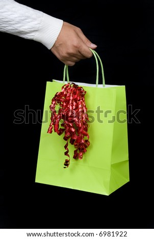 Holiday shopping bag with red bow waiting to be filled with gifts and goodies - stock photo