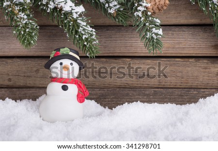 Holiday snowman figurine on snow with evergreen branches and wood background - stock photo