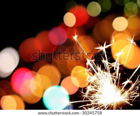 holiday sparkler and colorful lights - stock photo