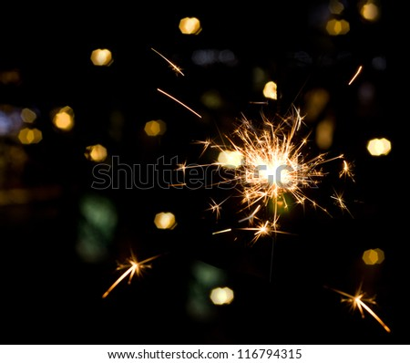 Holiday sparkler on colorful lights bokeh background - stock photo
