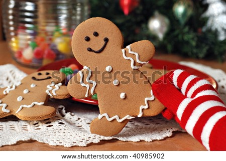 Holiday still life of colorful gloved hand holding a gingerbread man cookie.  Gumdrops and christmas tree in background.  Close-up with shallow dof. - stock photo