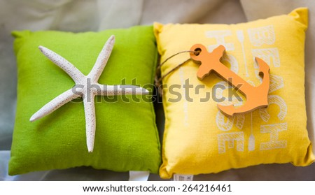 Holiday summertime travel concept - small toy pillows with starfish and anchor (small grip) - stock photo