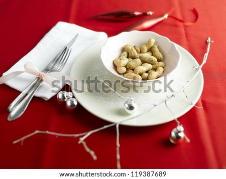 Holiday table setting in red with peanuts - stock photo