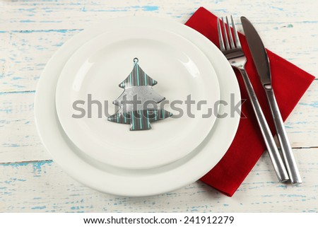 Holiday table setting with Christmas decoration on color wooden background - stock photo