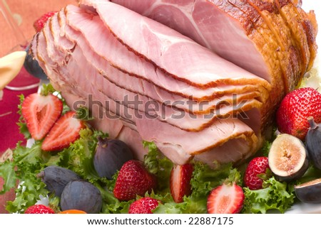 Holiday table setting with delicious whole baked sliced ham, fresh strawberries, figs, and vegetable salad. - stock photo