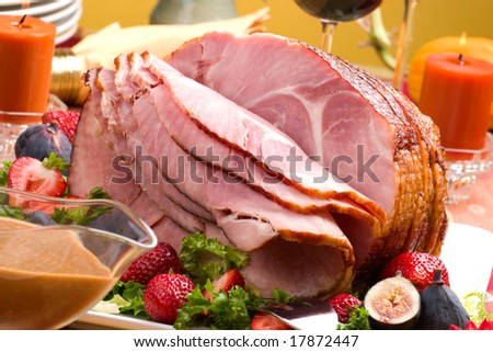 Holiday table setting with delicious whole baked sliced ham, fresh strawberries, figs, vegetable salad and glasses of red wine. - stock photo
