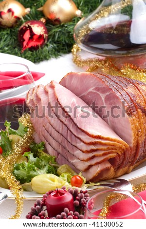 Holiday table setting with delicious whole baked sliced ham, marinated peppers, cherry tomatoes, vegetable salad and glasses of red wine. Christmas decoration, candles, ornaments around.