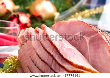 Holiday table setting with delicious whole baked sliced ham, vegetable salad and glasses of red wine. Christmas decoration, candles, ornaments around. - stock photo