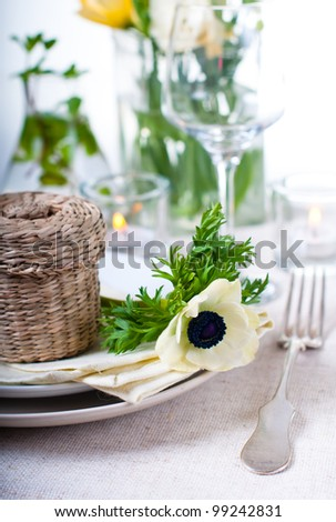 Holiday table setting with white flowers and candles - stock photo