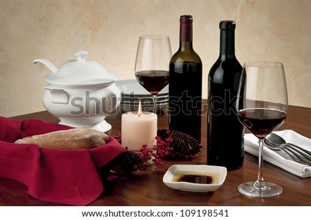 Holiday table setting with wine and simple festive props on wooden table top - stock photo