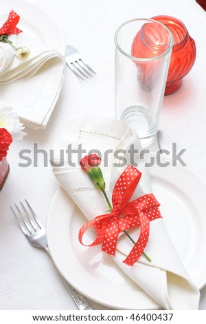 Holiday tableware in red and white colors with ribbons and flowers - stock photo