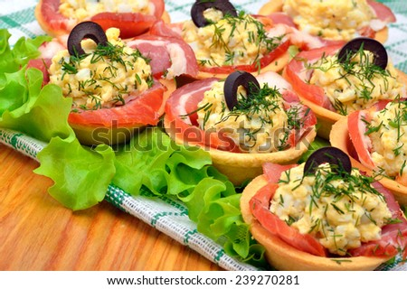 Holiday tartlets stuffed with eggs, ham, olives and green lettuce on the wooden background - stock photo