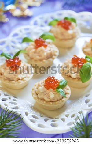 Holiday tartlets with seafood salad, red caviar and basil - stock photo