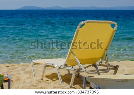 Holiday, Travel and Vacation concept with Sunbeds on the Sandy Beach near the Aegean Sea at beautiful summer day. - stock photo