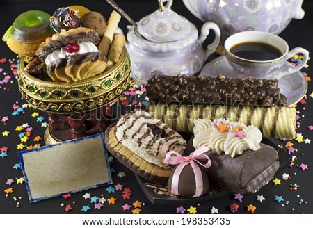 Holiday treating with card and tea set of dishes on black - stock photo