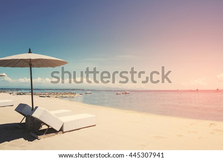 Holiday vacation at the beach, Beach deck chairs with parasol on tranquil beach, vintage tone soft focus - stock photo