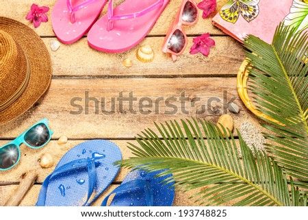 Holiday (vacation) tropical beach background layout with free text space. Palm tree leaves, sand, exotic flowers, sunglasses and flip flops on vintage wood - poster design. - stock photo