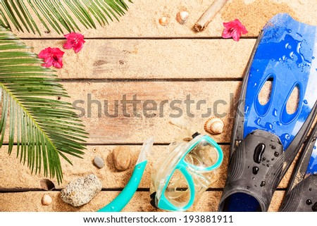 Holiday (vacation) tropical beach background layout with snorkeling theme and free text space. Flippers, goggles and snorkel on sand - diving equipment from above. - stock photo