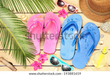 Holiday (vacation) tropical beach from above - palm tree leaves, exotic flowers, sunglasses and flip flops on sand. - stock photo