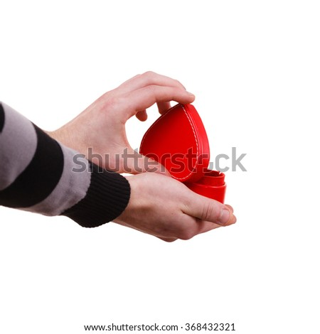 Holiday valentine day proposing concept. Man holding red heart shaped gift box in hand isolated - stock photo