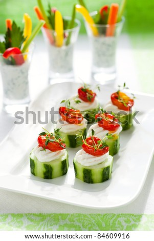 Holiday vegetable appetizers.Cucumbers with soft cheese and sun dried tomatoes and vegetable sticks with dip - stock photo