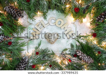 Holiday welcome sign with rope heart and green Christmas tree garland border, snow and lights on antique rustic wooden background
