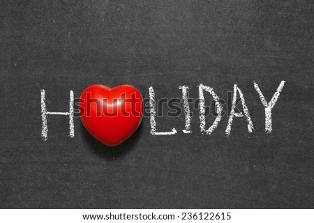 holiday word handwritten on chalkboard with heart symbol instead of O