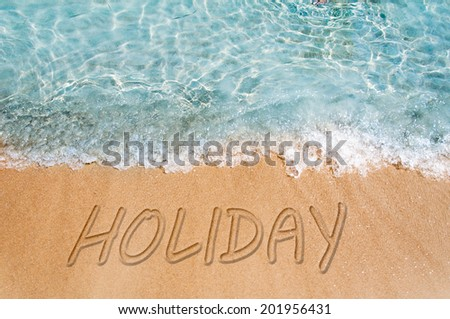 Holiday word sign on the beach sand  - stock photo