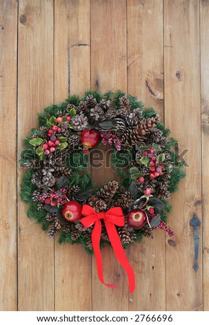 holiday wreath on pine door - stock photo