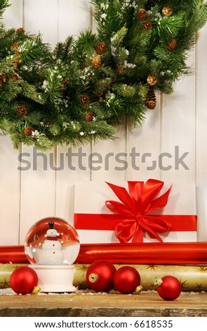 Holiday wreath with snow globe and red christmas balls - stock photo