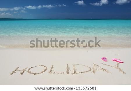 HOLIDAY writing on the sandy beach of Exuma, Bahamas - stock photo