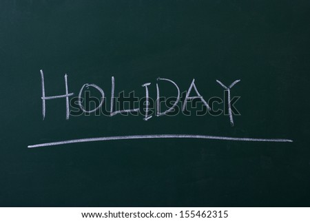 holiday written with chalk on chalkboard - stock photo