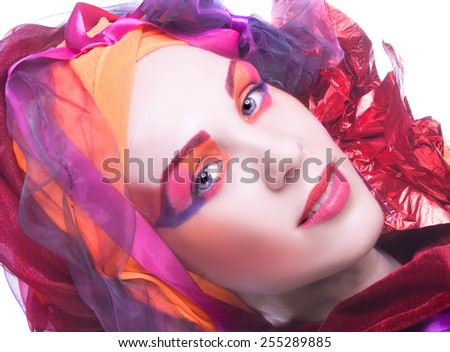 Holiday. Young woman in pink and red turban and with artistic visage. - stock photo