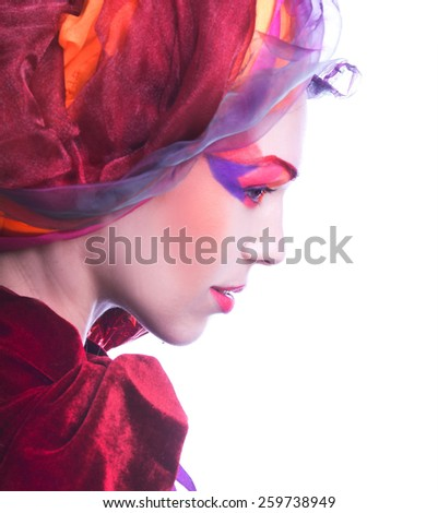 Holiday. Young woman in pink and red turban and with artistic visage.